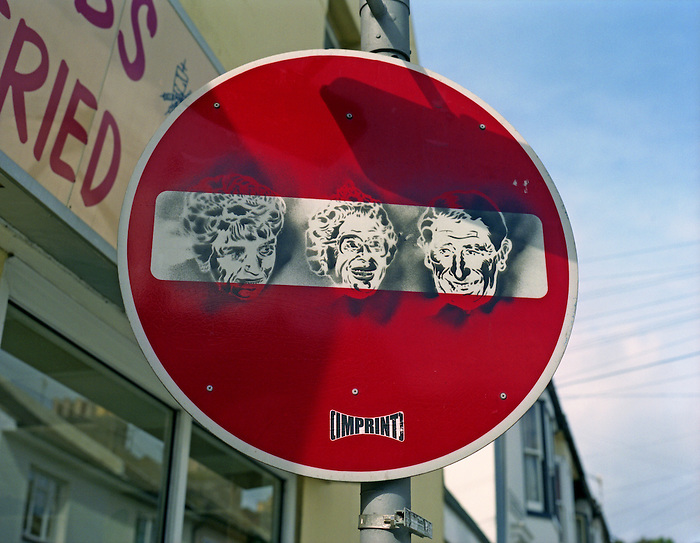 Stencil graffiti on a No Entry sign in Brighton depicts three members of the British Royal Family: Princess Diana, Queen Elizabeth II, and Prince Charles.