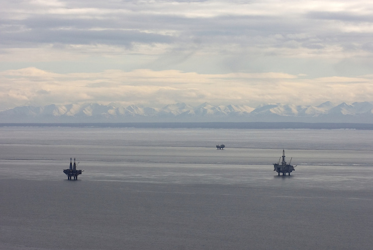 Oil and natural gas production platforms stand in Cook Inlet offshore from Nikiski and nearby Kenai, Alaska. The Kenai Mountains rise on the horizon of the Kenai Peninsula.