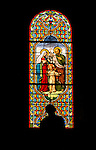 Stained glass window and statue in St. Pierre church in Blesle, France