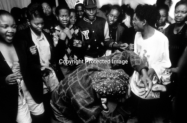 ditown00145 Unidentified people in a Shebeen, a (township bar) on April 23, 1997 in Soweto, South Africa. These shebeens are usually in someone's home where neighbors come to drink beer and watch sports on television. Party dancing.Photo: Per-Anders Pettersson/ iAfrika Photos