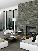 The family dog lies on a rug in the living area in front of the fireplace set in a slate wall