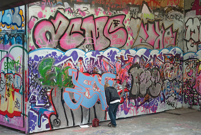 Young artist adds to the graffiti art on the walls of the skateboarding area under Queen Elizabeth Hall on the South Bank, London, England