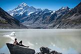NEW ZEALAND, Aoraki Mount Cook National Park, Woman Relaxing Next to Hooker Lake below Mount Cook, Ben M Thomas