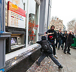 """© Joel Goodman - 07973 332324 . 26/03/2011 . London , UK . A black bloc of protesters carrying black and red anarcho-syndiclist flags smash windows and graffiti a branch of HSBC in Cambridge Circus . Hundreds of thousands of people attending an anti cuts demonstration under the banner """" March for the Alternative """" in central London , in protest at the coalition government's austerity measures . Photo credit : Joel Goodman"""