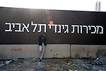 An African migrant stands aside near a construction site in Tel Aviv.