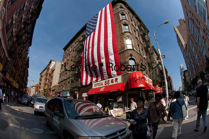 A giant American flag hangs from a building on Mott Street in the Little Italy neighborhood of New York on Friday, September 14, 2012.  The flag is displayed to remember the victims of the 9/11 terrorist attacks. (© Frances M. Roberts