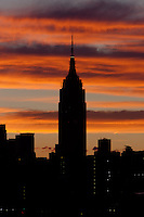 The Empire State Building and other Manhattan buildings are silhouetted against orange colored clouds shortly before sunrise.