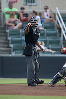 Home plate umpire Edwin Moscoso makes a strike call during the South Atlantic League game between the Asheville Tourists and the Kannapolis Intimidators at Intimidators Stadium on June 25, 2015 in Kannapolis, North Carolina.  The Intimidators defeated the Tourists 9-8.  (Brian Westerholt/Four Seam Images)