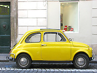 A bright yellow old Fiat Cinquecento parked in a central street of Rome.