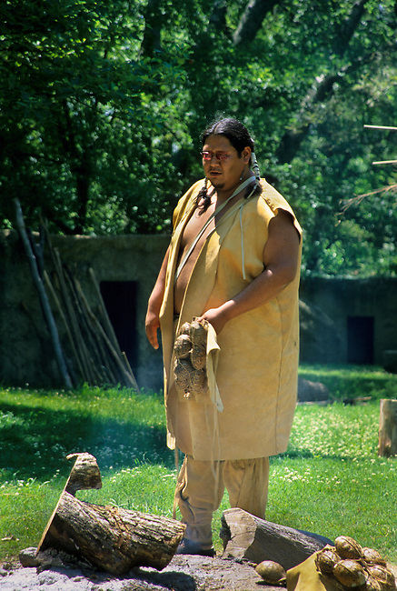 Cherokee man dressed in traditional buckskin clothing tells stories of his people near the eternal campfire in Tahlequay OK.