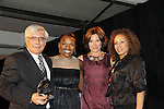 """Bill Solli is presented the Hearts of Gold Humanitarian Award by Countess LuAnn - L to R -  Deb Koenigsberger -  -Countess LuAnn de Lesseps [  Tamara Tunie at The Fourteenth Annual Hearts of Gold Gala """"Hooray for Hollywood!"""" - with its mission to foster sustainable change in lifestyle and levels of self-sufficiency for homeless mothers and their children on October 28, 2010 at the Metropolitan Pavillion, New York City, New York. (Photo by Sue Coflin/Max Photos)"""