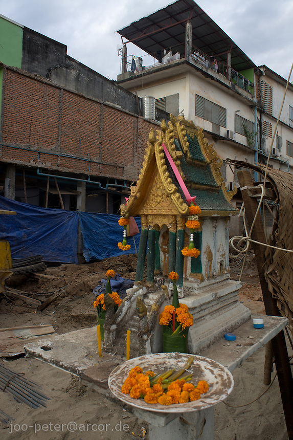 offerings in a miniature temple for local spirits next to a construction work area, capitol Vietiane, Laos, 2012
