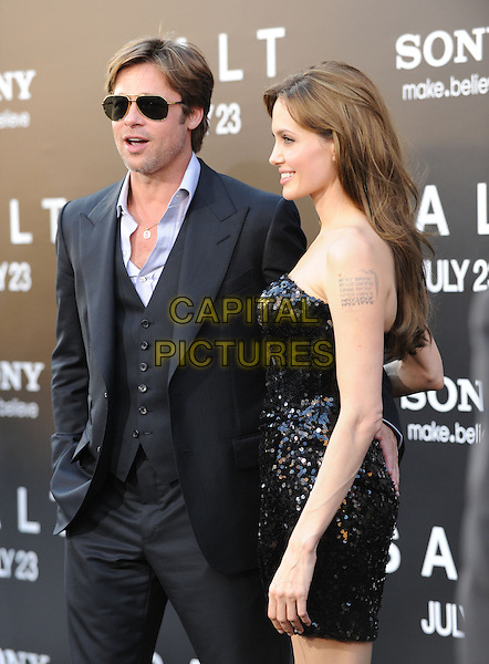 BRAD PITT & ANGELINA JOLIE.Premiere of SALT held at The Grauman's Chinese Theatre in Hollywood, California, USA. .July 19th, 2010         .half length black white shirt aviators suit strapless sequined sequin black dress couple sunglasses shades hand on back rear arm around waist profile unbuttoned tattoos .CAP/RKE/DVS.©DVS/RockinExposures/Capital Pictures.