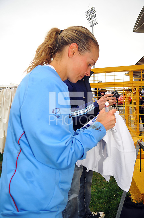Heather Mitts autographs a jersey for a fan. The USA defeated Norway 2-1 at Olhao Stadium on February 26, 2010 at the Algarve Cup.