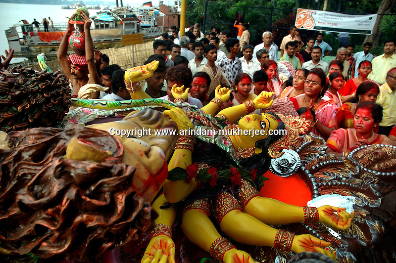 INDIA (West Bengal - Calcutta)  2006, Durga idol is being taken for immerssion on the last day of the festival. Its a ritual of drowning the idol in the Ganges after the worship is over. Durga Puja Festival is the biggest festival among bengalies.  As Calcutta is the capital of West Bengal and cultural hub of  the bengali community Durga puja is held with the maximum pomp and vigour. Ritualistic worship, food, drink, new clothes, visiting friends and relatives places and merryment is a part of it. In this festival the hindus worship a ten handed godess riding on a lion armed wth all possible deadly ancient weapons along with her 4 children (Ganesha - God for sucess, Saraswati - Goddess for arts and education, Laxmi - Goddess of wealth and prosperity, Kartikeya - The god of manly hood and beauty). Durga is symbolised as the women power in Indian Mythology.  In Calcutta people from all the religions enjoy these four days of festival in the moth of October. Now the religious festival has become the biggest cultural extravagenza of Calcutta the cultural capital of India. Artistry and craftsmanship can be seen in different sizes and shapes in form of the idol, the interior decor and as well as the pandals erected on the streets, roads and  parks.- Arindam Mukherjee