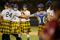 Savannah Bananas pitcher Zachary Cable (24) shakes hands with catcher Bill Leroy (1) after closing out a Coastal Plain League game against the Macon Bacon on July 15, 2020 at Grayson Stadium in Savannah, Georgia.  Savannah wore kilts for their St. Patrick's Day in July promotion.  (Mike Janes/Four Seam Images)