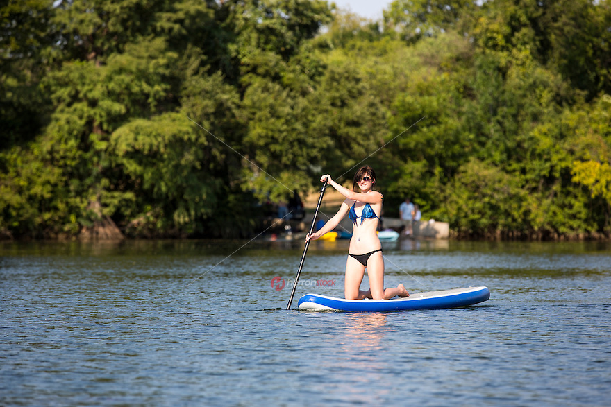 Woman on Stand Up Paddle Board, SUP, exercises on Lady Bird Town Lake in Austin, Texas - Stock Image