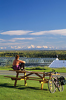 University of Alaska student enjoys the sunny autumn weather and view of the Alaska Range from the lawn of the UAF museum, Fairbanks, Alaska.
