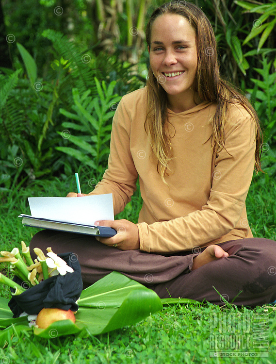 Young woman writing in journal and making ti leaf hookupu offering on a Big Island retreat at Kalani Honua