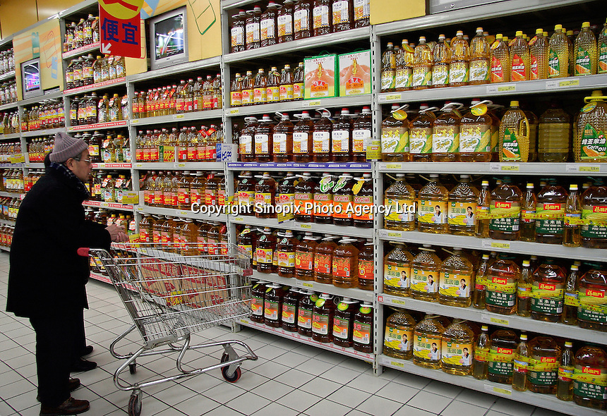A shopper checks out a variety of cooking oil on offer at a Carrefour Supermarket in Shanghai, China. According to a recent report, China has surpassed the United States in total consumption of every basic food, energy, and industrial commodity except oil, as well as goods such as television sets, refrigerators and mobile phones. However the per capita income for China is only roughly one seventh of that of the U.S..19 Feb 2005