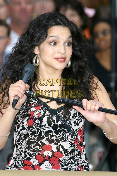 NORA JONES.Performs at The Today Show Summer Concert Series at Rockafeller Plaza in New York..July 30, 2004 .headshot, portrait, hoop earrings, funny, grabbing microphone, gesture.www.capitalpictures.com.sales@capitalpictures.com.©Capital PIctures