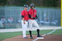 Kannapolis Intimidators manager Justin Jirschele (9) chats with Joel Booker (23) as he stands on third base during the game against the Lakewood BlueClaws at Kannapolis Intimidators Stadium on April 8, 2017 in Kannapolis, North Carolina.  The BlueClaws defeated the Intimidators 8-4 in 10 innings.  (Brian Westerholt/Four Seam Images)