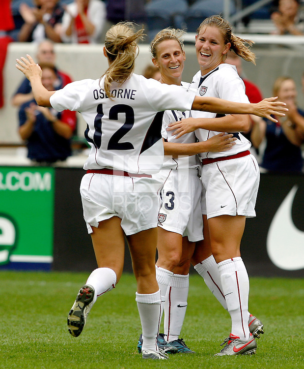 USA midfielder Leslie Osborne (12) and forward Kristine Lilly (13) congratulate Cat Whitehill (4) after Whitehill scored to tie the game 1-1.  The U.S. Women's National Team defeated China 4-1 at Toyota Park in Bridgeview, IL on August 28, 2006.