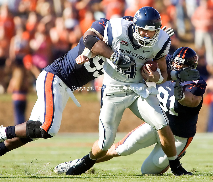 CHARLOTTESVILLE, VA- 13 OCT 2007- 101307JT13- <br /> UConn's Tyler Lorenzen gets tackled by Virginia's Jeffrey Fitzgerald, left, during the first quarter of Saturday's game at Virginia. UConn lost 16-17.<br /> Josalee Thrift / Republican-American