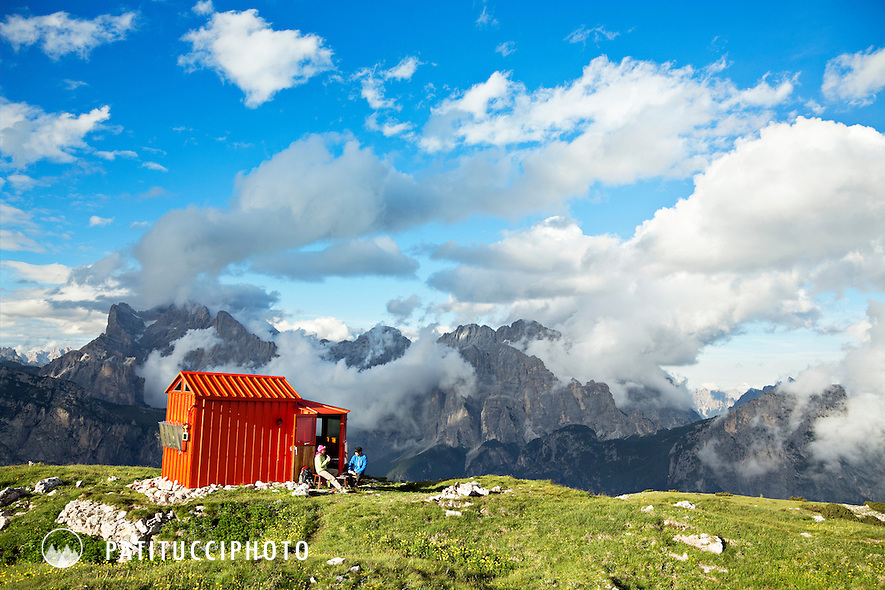 A couple outside the Bedin Bivouac Hut in the Italian Dolomites playing cards