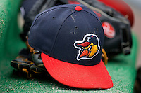 A Toledo Mudhens cap sits on top of a glove in the visitors dugout at Harbor Park June 7, 2009 in Norfolk, Virginia. (Photo by Brian Westerholt / Four Seam Images)