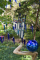 Blue glass bottle garden with matching gazing ball in shade for unexpected quirky style in garden ornaments and accessories