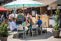Foodies enjoy the offerings at the Urban Bites outdoor market in Penn Plaza in New York on Sunday, June 14, 2015. The popular seasonal food fair, in a previously underused pass through space which attracted the homeless,  brings an assortment of restaurants providing an outdoor dining experience attracting hungry office workers in the area, shoppers and tourists. (© Richard B. Levine)