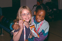 Friends age 7 laughing on Youth Express community bowling party.  St Paul  Minnesota USA