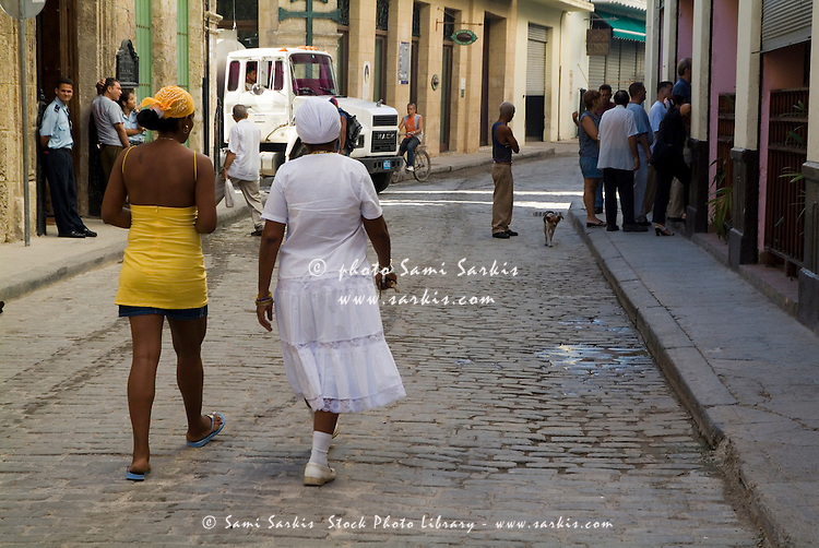 Women walking down a city street together near Plaza Vieja, Havana, Cuba.