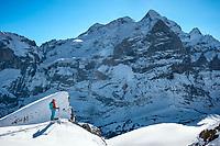 A ski tourer stands looking at the Wetterhorn, Grindelwald, Switzerland
