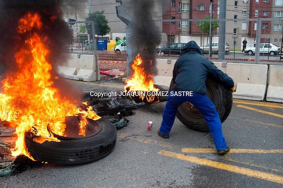 18 JUNIO 2012.LANGREO-ASTURIAS.Un minero quema una rueda en una barricada en Langreo con motivo del dia de huelga general.foto JOAQUIN GOMEZ SASTRE