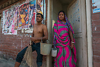 Bangladesh, Jhenaidah. Neema and her husband are caretakers for the public toilets in the local market. She collects the money and he cleans them. They collect 2 TK each for about 100 customers a day so they make about 200 TKs or $2 a day. they live in a local slum and have one daughter. He tends to take the money and drink.  Most of these people living in this slum are Dalit Hindu, or the untouchable caste working as sweepers and toilet cleaners. There are about 5.5 million Dalit across the country, they are most neglected caste in their society. The SNV Development Organization is providing fecal sludge management and occupational safety training for toilet and septic tank cleaners. In front of the toilets. Model released.