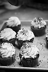 Cupcakes on a tray in a commercial kitchen. Black and white image.