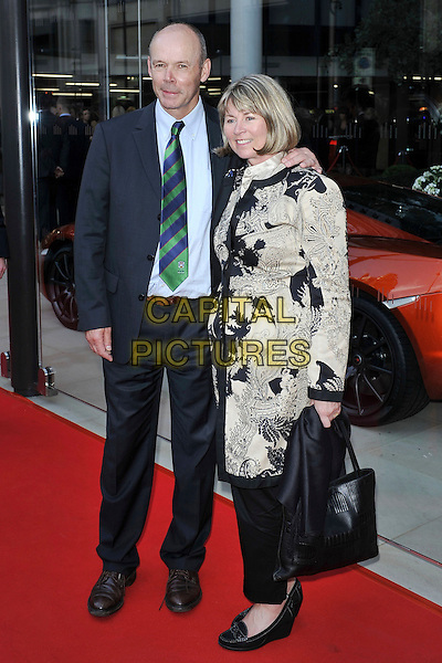 Sir Clive Woodward & guest .attending the McLaren Car Showroom Launch at One Hyde Park, Knightsbridge, London, England, UK, June 21st 2011..full length suit arm around  beige black print  blue shirt green tie  striped couple  bag coat .CAP/MAR.© Martin Harris/Capital Pictures.