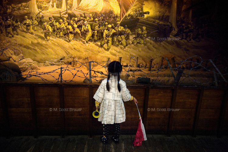 A young girl looks at a mural depicting a 20th century Communist uprising in Nanjing, China, at the Yuhuatai Museum of Revolutionary Martyrs in Nanjing, China.