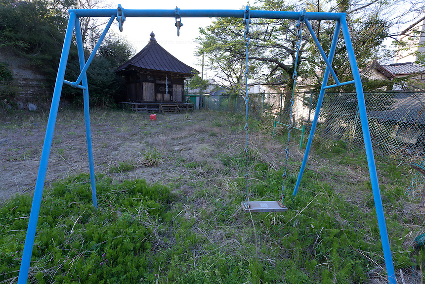 A playground swing in a shrine in the town of Tomioka, Futaba District of Fukushima, Japan. Monday April 29th 2013. The town was evacuated on March 12th after the March 11th 2011 earthquake and tsunami cause meltdowns at the nearby Fukushima Daichi nuclear power station. It lies well within the 20 kms exclusion zone though parts of the town have recently been opened again to allow locals to visit their property during daylight hours.