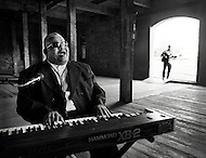 An elderly african-american blues musician plays the keyboard and sings along with his guitarist in an old tobacco warehouse in Durham, North Carolina.