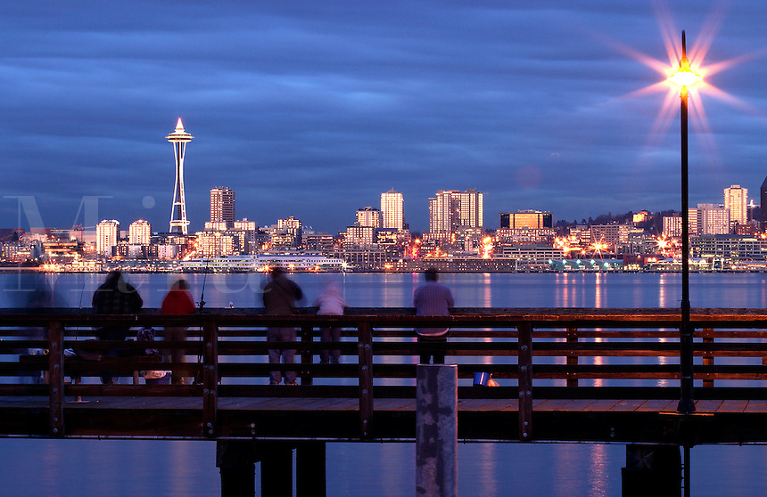 Fishermen on pier with Seattle skyline and Elliot Bay viewed from West Seattle, Seattle, Washington, US