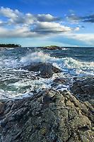 Brytande våg över klippa vid havet i Stockholms skärgård.