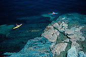 Kayakers along a rocky shore on Lake Superior