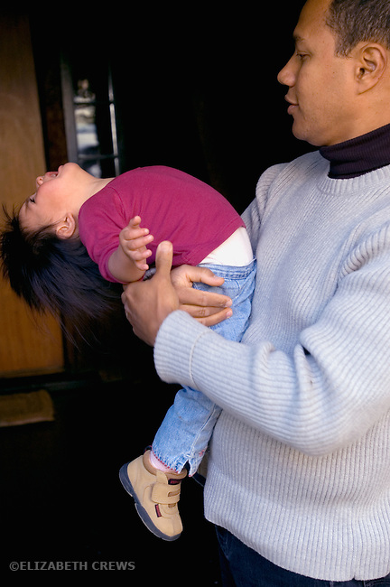 Berkeley CA Cuban father dealing with adopted Guatemalan daughter's tantrum, her back arched in rage.  Child, eighteen-months-old MR