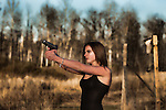 Young woman shooting a handgun