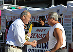 Bellmore, New York, USA. 20th September 2015. U.S. Senator CHARLES (CHUCK) SCHUMER (Democrat - New York) shakes hands with a fair-goer and eats corn on the cob at the 29th Annual Bellmore Family Street Festival, featuring family fun with exhibits and attractions, with over 100,000 people expected to attend over the weekend.