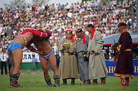Ulaanbaatar, Mongolia, July 2003..Competitors in the Mongolian Wrestling championships in the national Naadam at Ulaanbaatar central stadium. Judges consult the rule-book during the 3 hour semi-final match which threatened to turn into a stalemate.