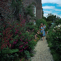 Francesca Rowan walks down a gravel path in the garden which runs along the side of Lamb House